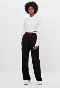 Bershka - MIT WEITEM BEIN - Trousers - black - 1