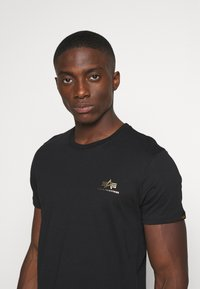 Alpha Industries - BASIC SMALL LOGO FOIL PRINT - Basic T-shirt - black/yellow gold - 3