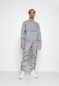 Hi-Tec - GRAHAM REFLECTIVE TRACK PANTS - Tracksuit bottoms - silver - 1
