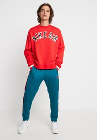 Nike Sportswear - PANT TRIBUTE - Tracksuit bottoms - geode teal/university red - 1