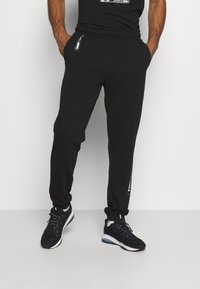 Puma - NU TILITY PANTS - Tracksuit bottoms - black - 0
