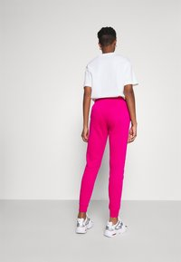 Nike Sportswear - Tracksuit bottoms - fireberry/white - 2