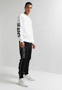Calvin Klein - LOGO PRINT - Pantaloni sportivi - perfect black - 1