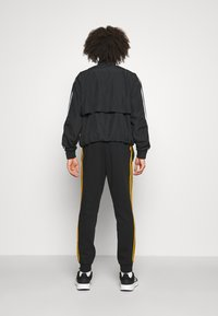 adidas Performance - 3 STRIPES  ESSENTIALS - Tracksuit bottoms - black/semi solar gold - 2
