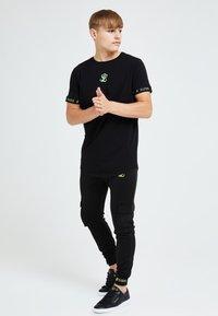 Illusive London Juniors - Trainingsbroek - black & green - 0