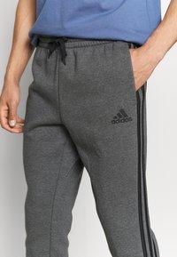 adidas Performance - 3 STRIPES  ESSENTIALS - Tracksuit bottoms - dark grey heather/black - 4