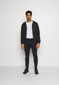 Calvin Klein Golf - ULTRON HOODED JACKET - Waterproof jacket - black - 1