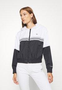 Calvin Klein Jeans - STRIPE TAPE HOODED WINDBREAKER - Summer jacket - black - 0
