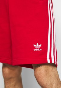 adidas Originals - 3-STRIPE UNISEX - Tracksuit bottoms - red - 5