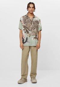 Bershka - MIT WEITEM BEIN UND BUNDFALTEN  - Relaxed fit jeans - beige - 1