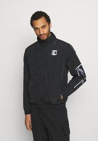 Karl Kani - SIGNATURE TRACKJACKET UNISEX - Summer jacket - black - 0
