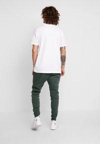 Nike Sportswear - Spodnie treningowe - galactic jade/black - 2