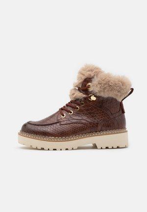BOOTS - Kotníkové boty na platformě - brandy