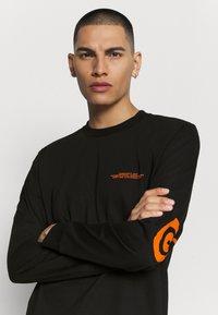 Carhartt WIP - INTERNATIONAL OPERATIONS  - Long sleeved top - black/orange - 3