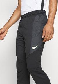 Nike Performance - DRY STRIKE WINTERIZED - Tracksuit bottoms - black/volt - 3