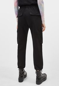 Bershka - CARGOPANTS - Trousers - black