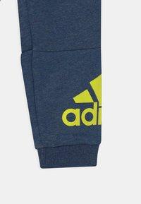 adidas Performance - UNISEX - Tracksuit bottoms - dark blue/neon yellow - 2