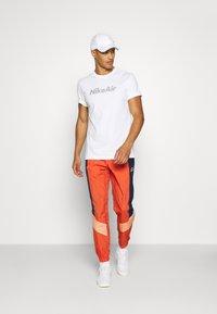 Nike Sportswear - Tracksuit bottoms - mantra orange/obsidian/orange frost - 1