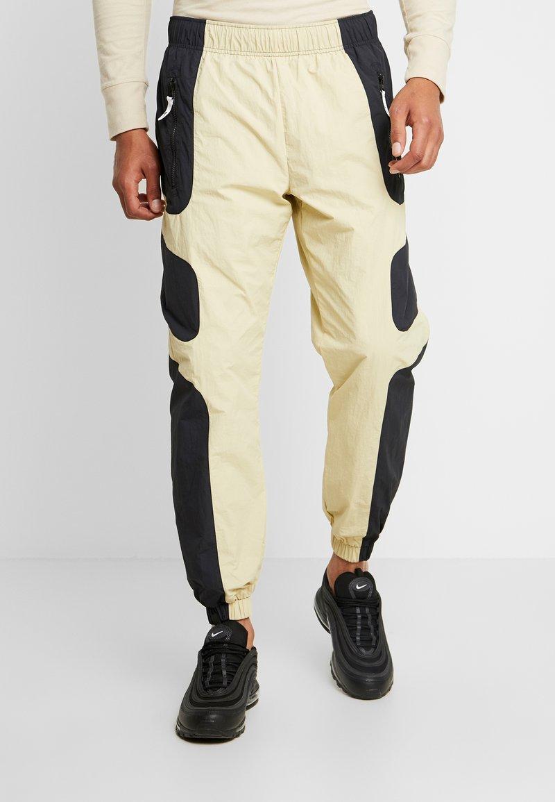 Nike Sportswear - RE-ISSUE - Pantalon de survêtement - black/team gold