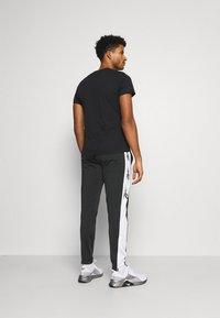 Reebok - VECTOR TRACK PANT - Pantalon de survêtement - black - 2