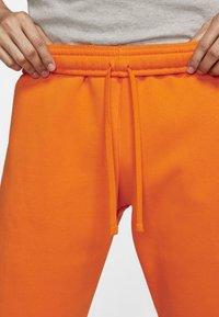 Nike Sportswear - CLUB - Tracksuit bottoms - magma orange/white - 2