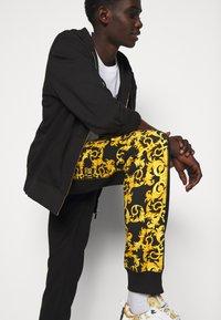 Versace Jeans Couture - PRINT LOGO BAROQUE - Teplákové kalhoty - black - 3