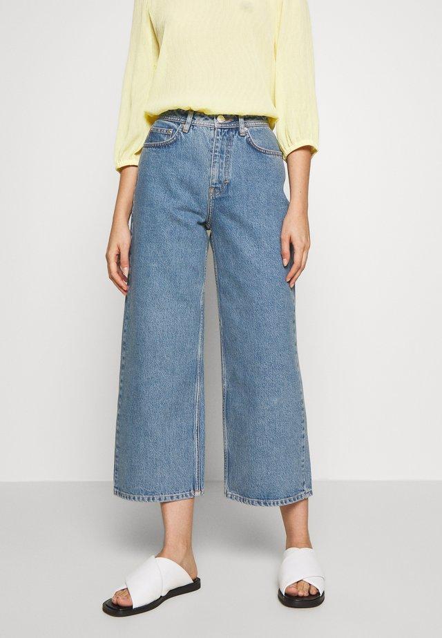 KIRI EXCLUSIVE - Flared Jeans - distressed blue
