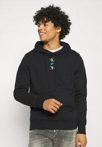 Calvin Klein Jeans - REPEAT TEXT GRAPHIC HOODIE UNISEX - Hoodie - black - 0