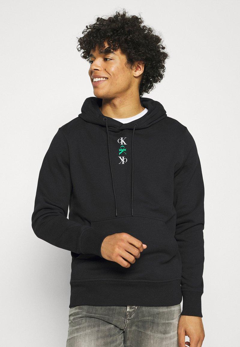 Calvin Klein Jeans - REPEAT TEXT GRAPHIC HOODIE UNISEX - Hoodie - black