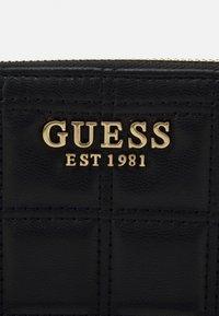 Guess - KAMINA LARGE ZIP AROUND - Wallet - black - 4