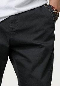 Tigha - Trousers - black - 3