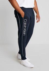 Calvin Klein - LOGO PRINT PANT - Träningsbyxor - blue - 0
