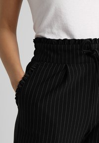 ONLY Petite - ONLPOPTRASH CLASSI PINSTRIPE FRILL - Trousers - black - 5