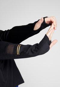 Nike Performance - GLAM MID PLUS - Funkční triko - black/metallic gold - 3