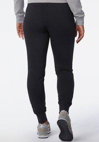 New Balance - Tracksuit bottoms - black - 1