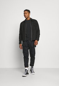 Converse - PANELED JOGGER - Cargo trousers - black - 1