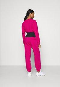 Nike Sportswear - Tracksuit bottoms - fireberry/black/white - 2
