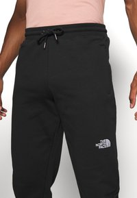 The North Face - MEDIUM - Tracksuit bottoms - black - 5