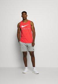 Nike Performance - TANK ATHLETE - Sports shirt - track red - 1