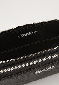 Calvin Klein - SIDED DOUBLE ZIPAROUND WALLET - Wallet - black - 4