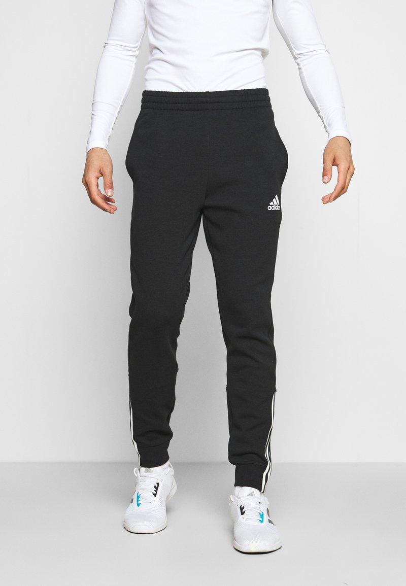adidas Performance - DK ESSENTIALS - Tracksuit bottoms - black/white