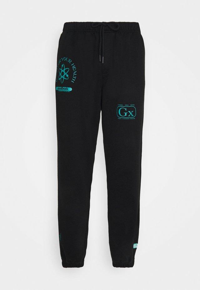 PILLS PANTS - Teplákové kalhoty - black