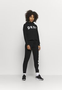 DKNY - EXPLODED LOGO CUFFED - Tracksuit bottoms - black - 1