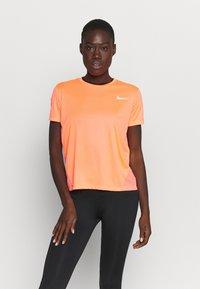 Nike Performance - MILER - T-shirt med print - bright mango/silver - 0