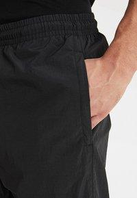 Urban Classics - CRINKLE TRACK PANTS - Tracksuit bottoms - black/white/ultraviolet - 3
