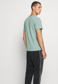 Nike Sportswear - REPEAT - Tracksuit bottoms - black - 3