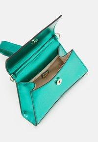 Guess - DEVIN CROSSBODY WRISTLET - Handbag - green - 2