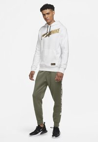 Nike Sportswear - REPEAT - Tracksuit bottoms - medium olive - 1