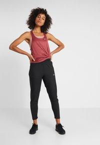 Nike Performance - Tracksuit bottoms - black/reflective silver - 1
